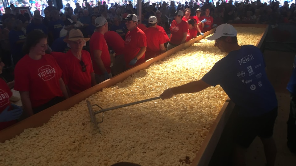 Un homme étend du fromage sur une poutine géante.