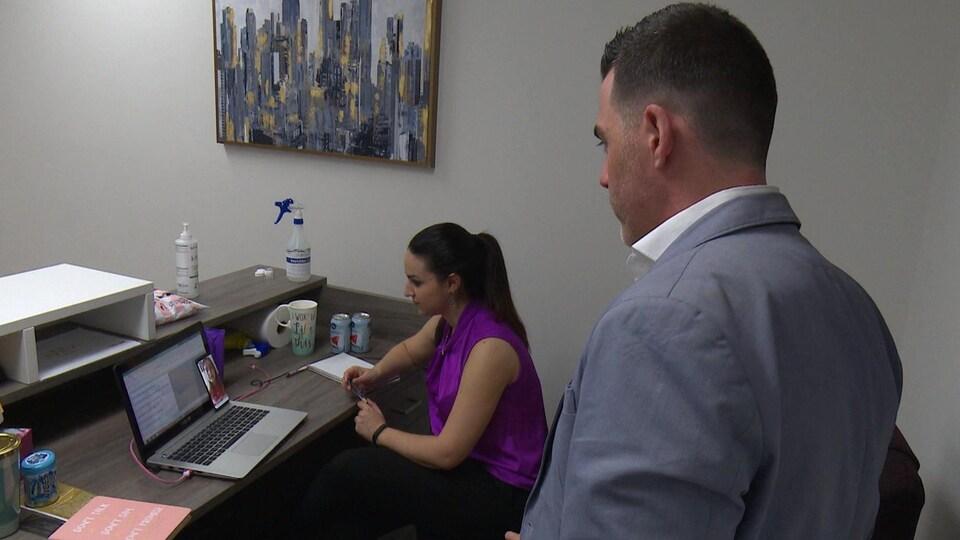 Un homme debout et une femme assise tiennent une conversation avec une femme par vidéoconférence sur un téléphone portable.