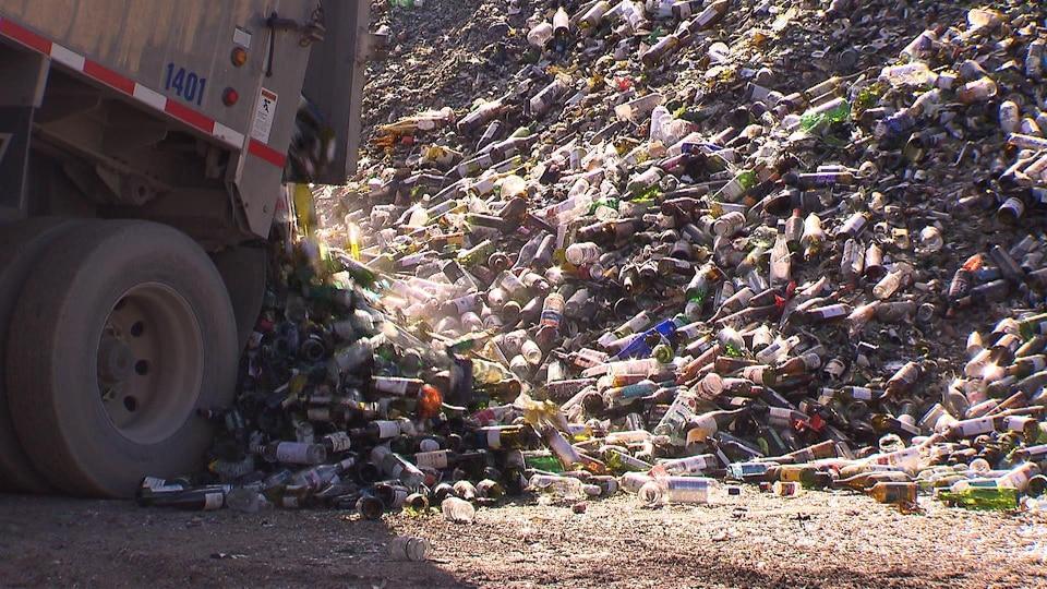 Un camion décharge sa cargaison de bouteilles de verre dans un site de récupération.