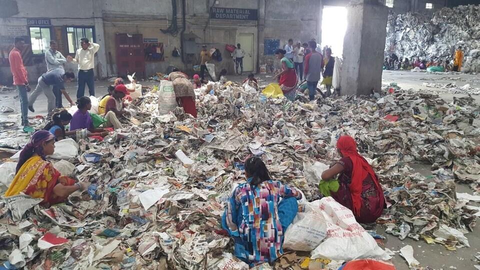 Des travailleuses indiennes assises par terre sur des amoncellements de papier.
