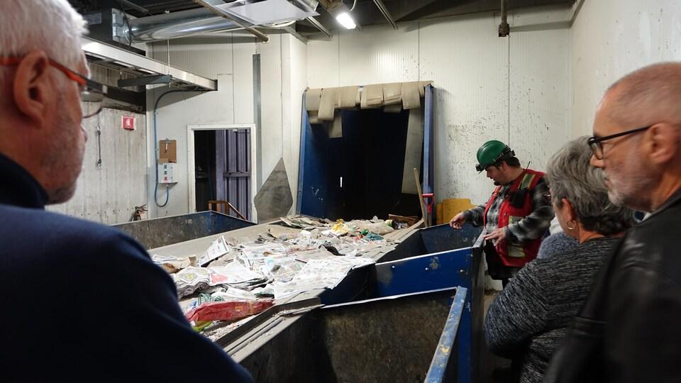 Un employé du centre de tri explique à des visiteurs le fonctionnement d'une chaîne de travail.