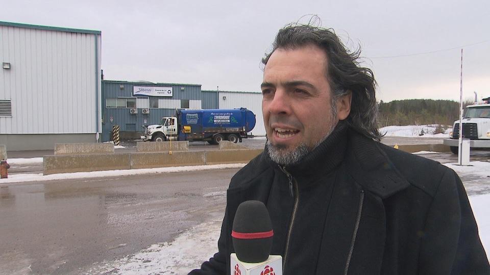Un homme parle au micro devant un édifice et un camion de recyclage