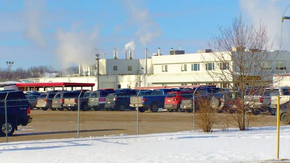 Des voitures garées devant une usine.