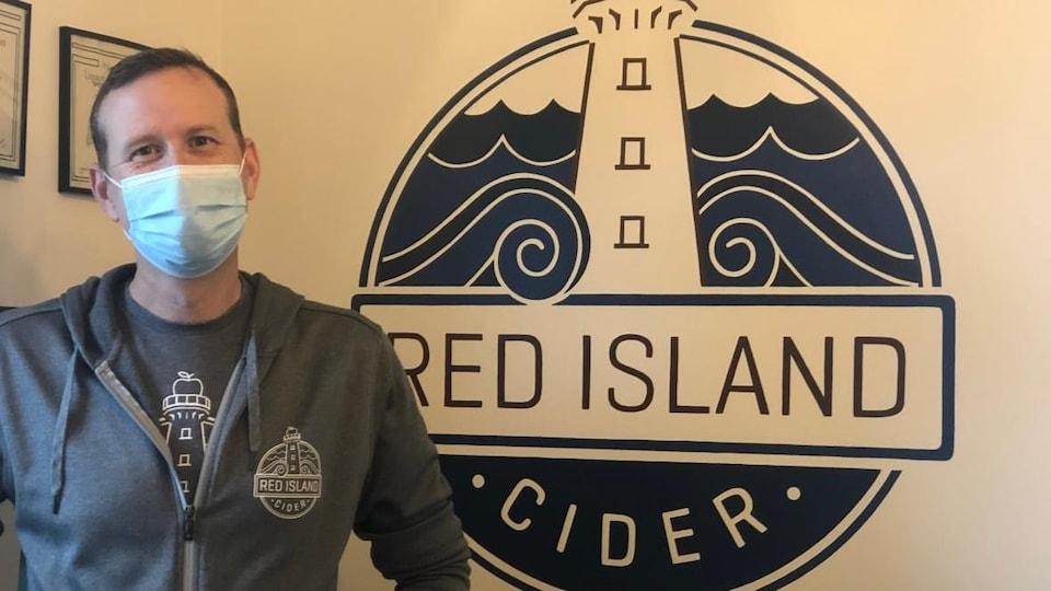 Rod Weatherbie pose pour la photo devant le logo de son entreprise.