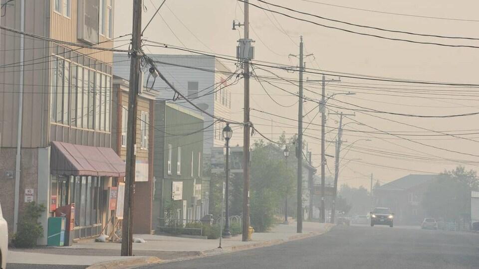 Une rue presque déserte et enfumée.