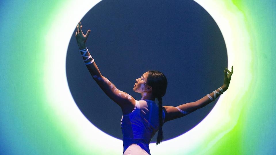 Une femme apparaît au premier plan, devant une forme circulaire cerclée d'un halo lumineux