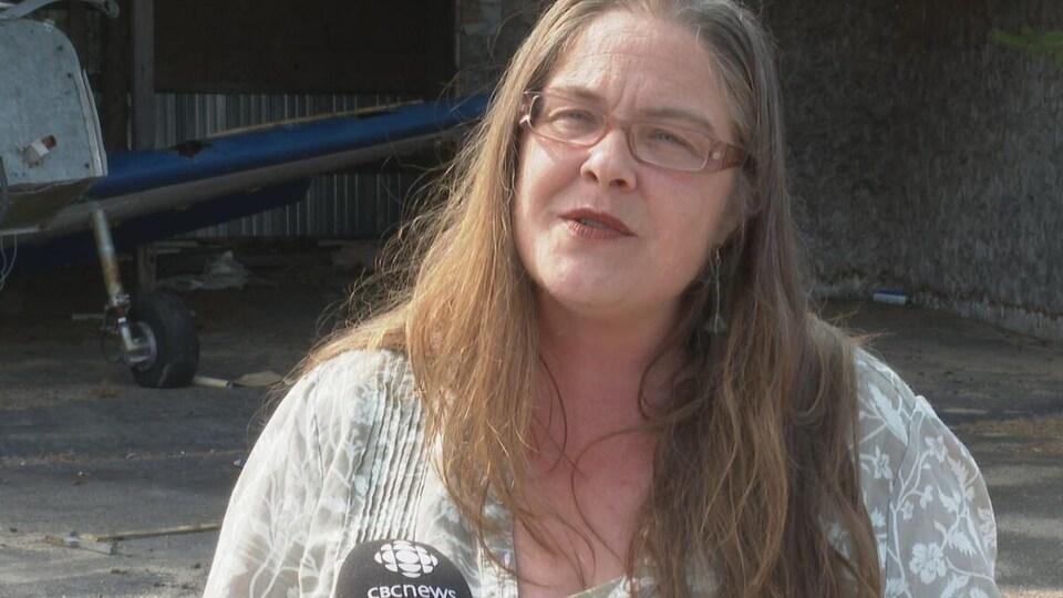 Kimberly Reeder interviewée devant un bâtiment de l'aérodrome.