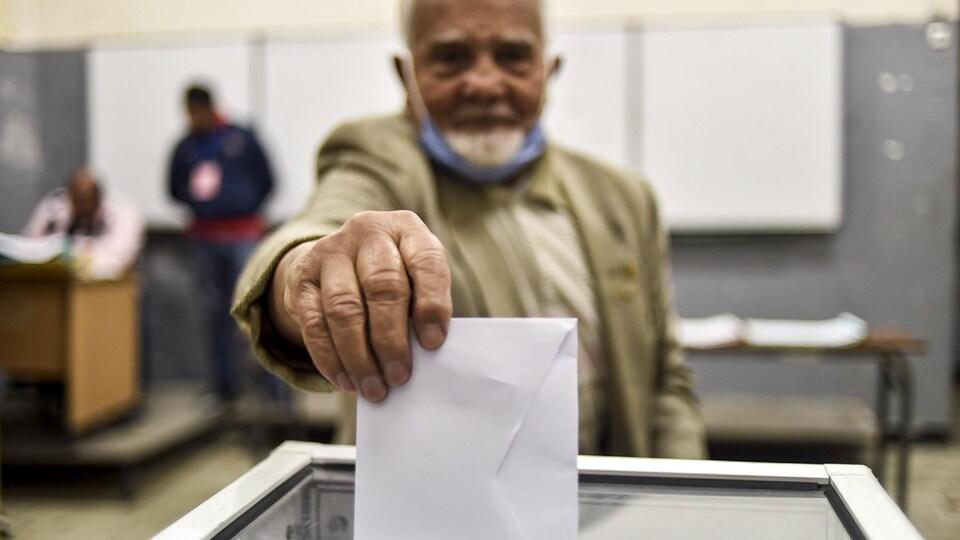 Un vieil homme dépose son bulletin de vote dans une urne.
