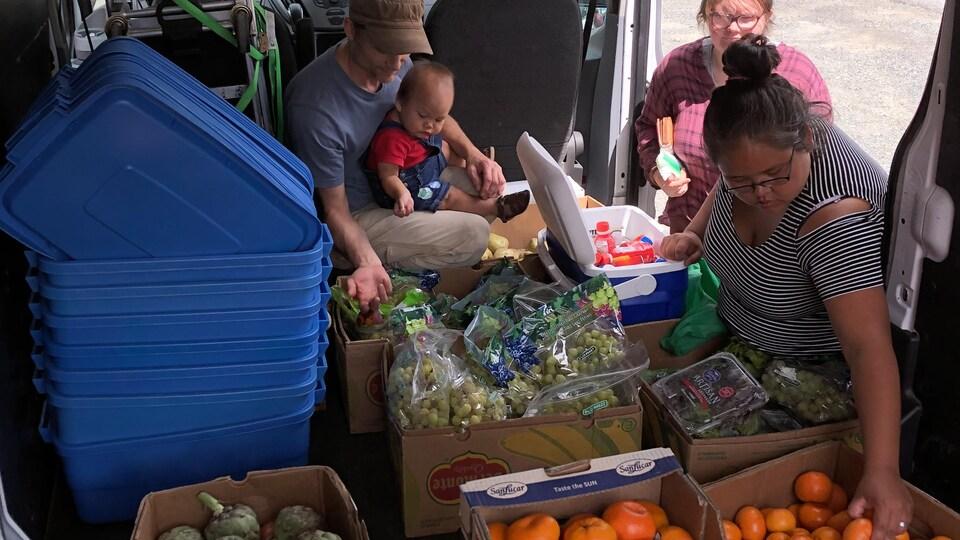 Des gens trient des fruits dans des boîtes à l'intérieur d'une fourgonnette.