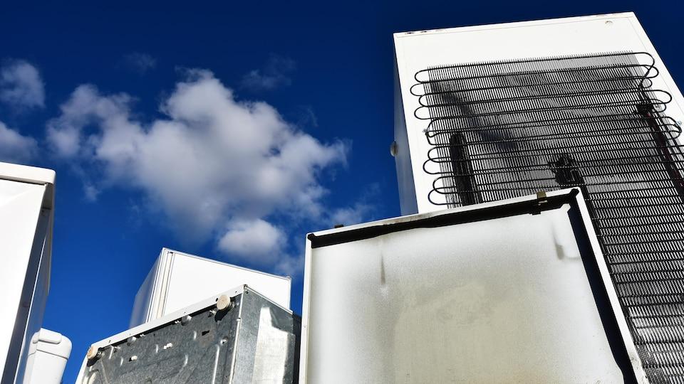 On voit de vieux électroménagers et un ciel bleu.