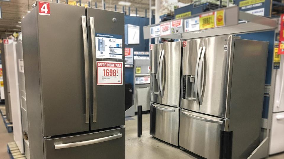 Des réfrigérateurs argentés, dont le congélateur se situe en bas, sont présentés les uns à côté des autres dans un coin du magasin d'électroménagers. Des étiquettes rouges sont notamment apposées sur les électroménagers.