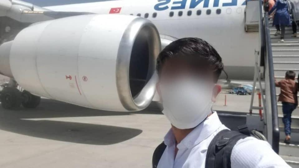 Un jeune homme avec un masque et au visage flouté se prend en photo devant un avion.