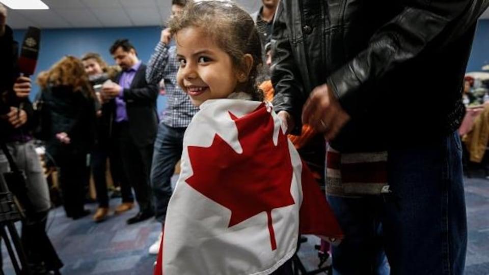 Une jeune fille porte un drapeau canadien sur son dos dans une salle où se retrouvent une dizaine de personnes.