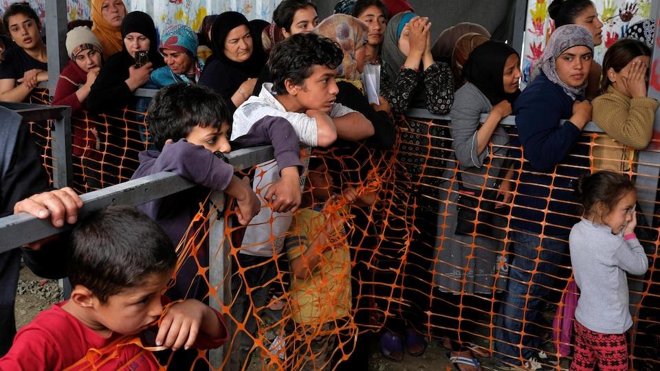 Plusieurs enfants et femmes en file derrière une barrière.