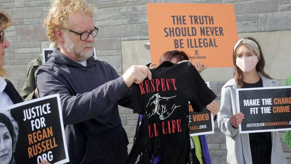 Un homme tient un t-shirt noir