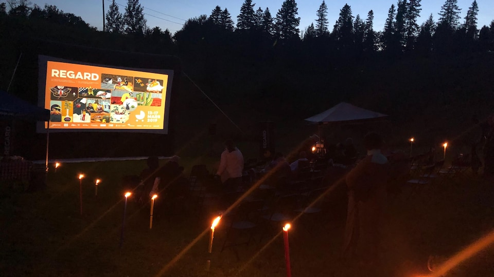 Une projection de film à l'extérieur sur un écran.