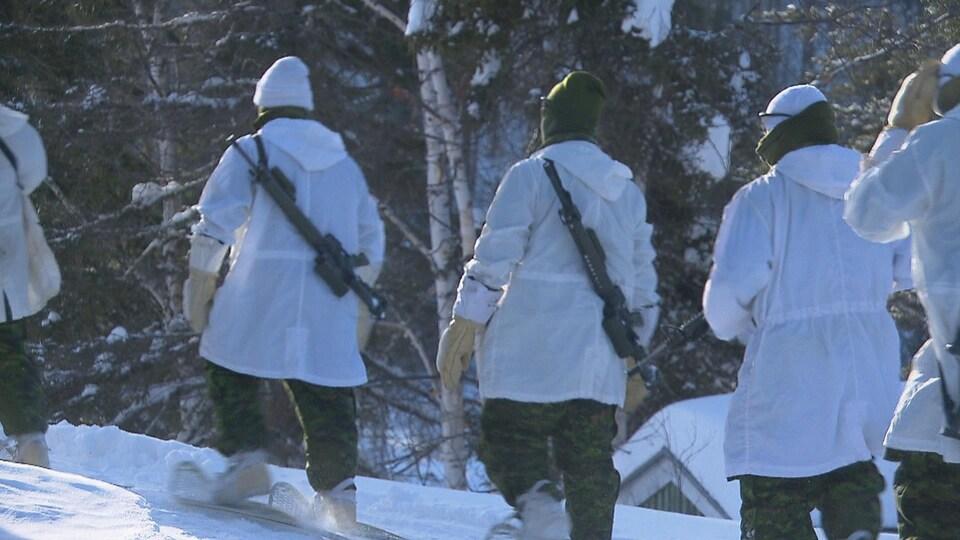 Des militaires du Régiment du Saguenay marchent dehors en plein hiver.