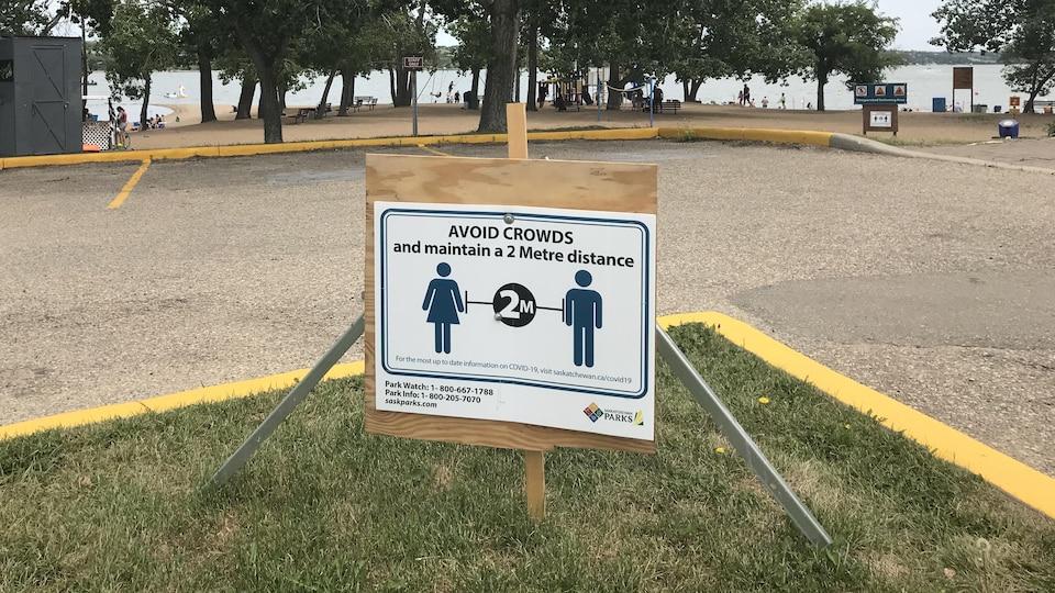Une pancarte, près d'une plage, qui demande de se tenir à 2 mètres d'une autre personne.