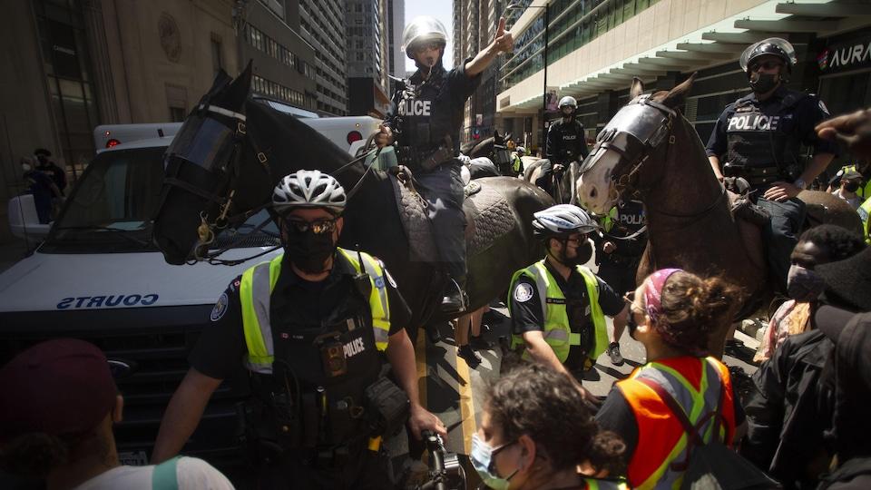 Des policiers entourent un fourgon à la suite d'une arrestation lors de la marche pour marquer le premier anniversaire de la mort de Regis Korchinski-Paquet.