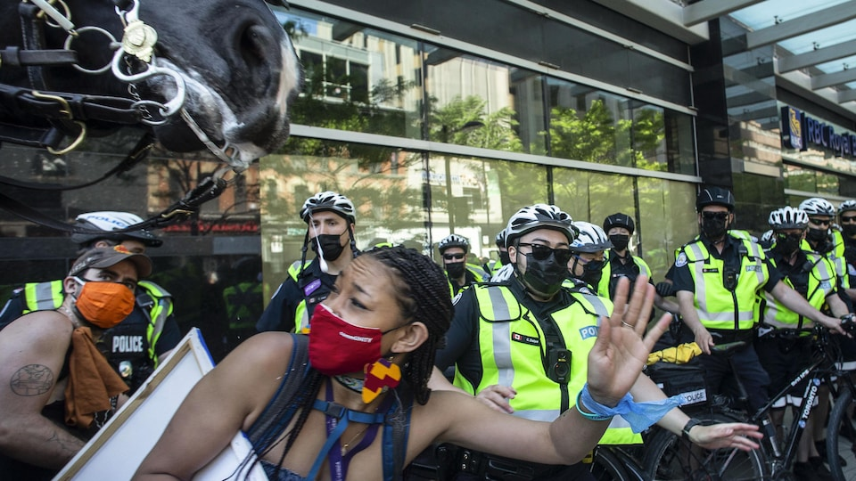 Des manifestants s'écartent en vitesse quand un policier à cheval se fraie un passage dans la foule à la marche anniversaire du 24 mai.