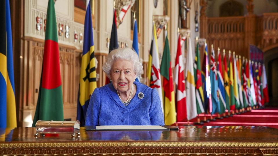 La reine, assise à un bureau devant les nombreux drapeaux des pays faisant partie du Commonwealth.