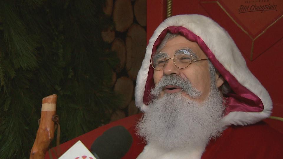 Avec ses vêtements rouges et sa barbe blanche, le père Noël est souriant.