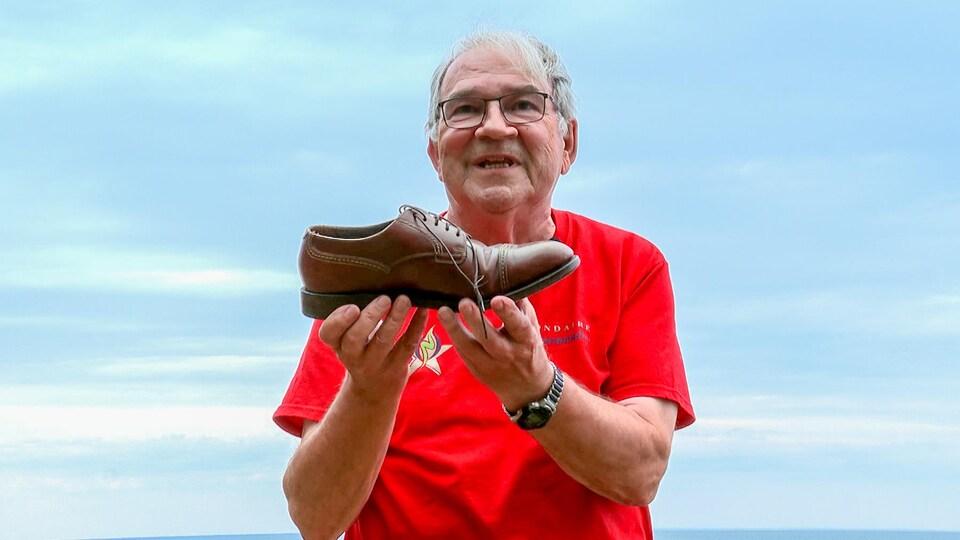 Réjean Boivin montre un soulier.