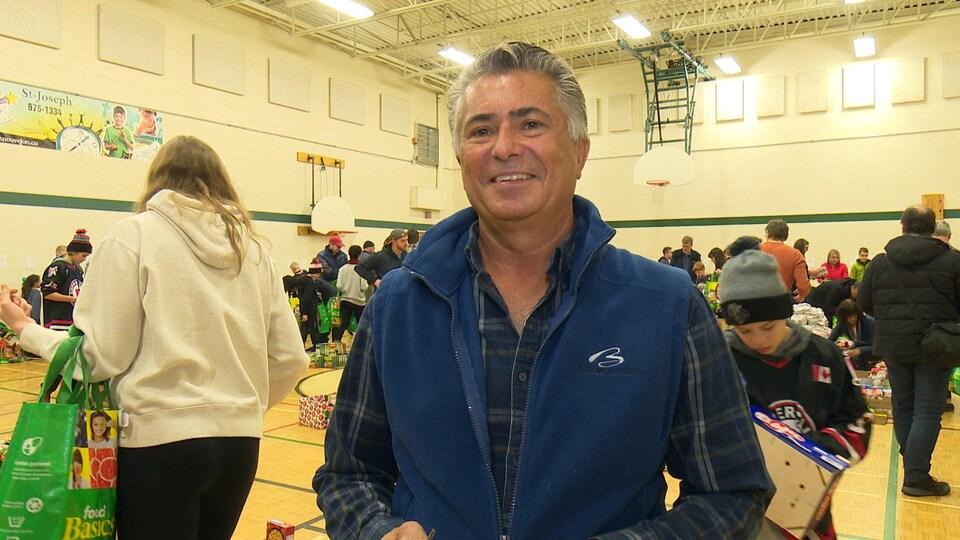 Réjean Dupuis sourit debout dans un gymnase bondé.