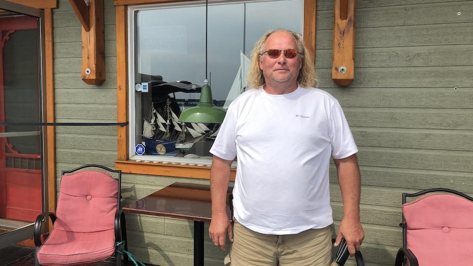 Réjean Sini  est sur le balcon d'une maison et porte des lunettes de soleil.