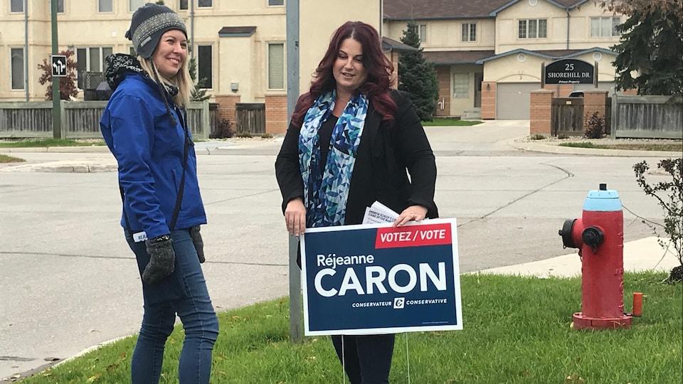 Réjeanne Caron et Michelle Rempel installent une pancarte électorale sur une pelouse.