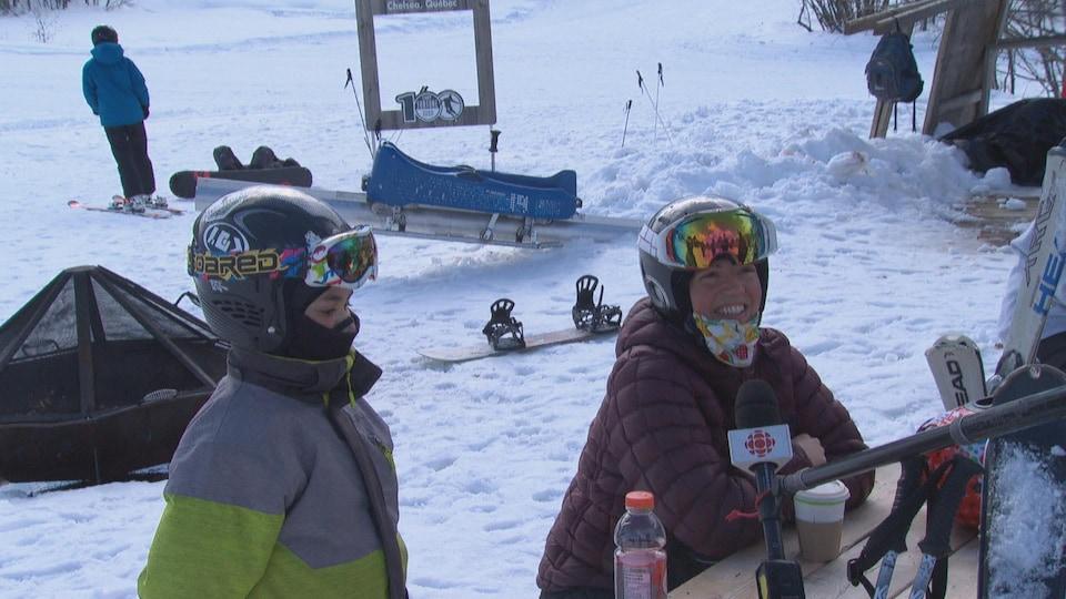 Une femme accorde une entrevue à la caméra, au pied d'une station de ski.