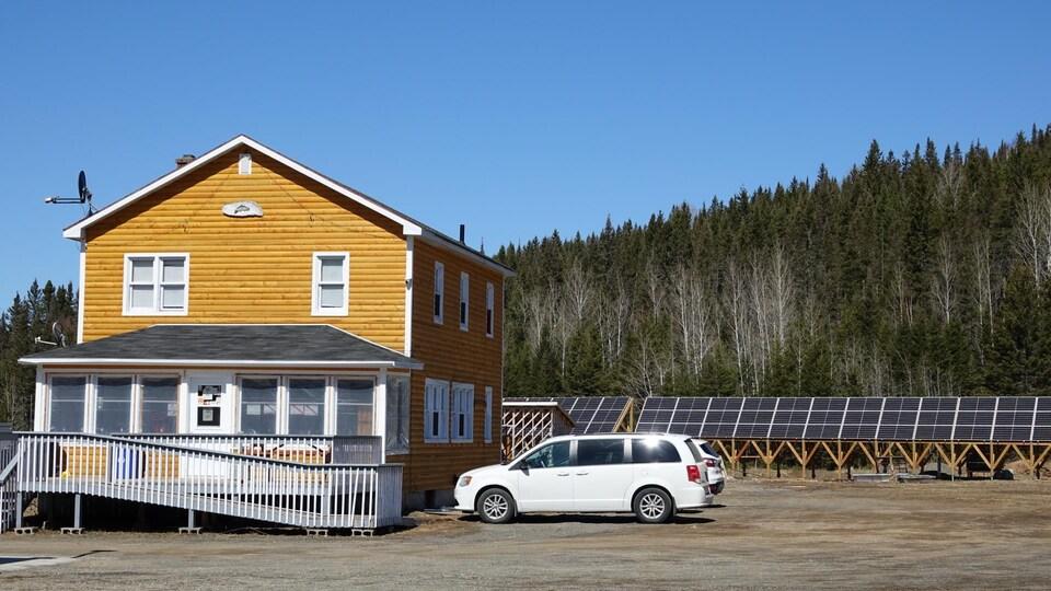 Un bâtiment en bois rond avec des panneaux solaires à l'arrière.
