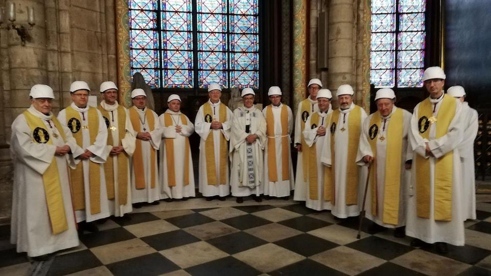 Mgr Michel Aupetit pose avec d'autres membres du clergé après la première messe dans une chapelle latérale, deux mois jour pour jour après l'incendie de la cathédrale Notre-Dame de Paris.