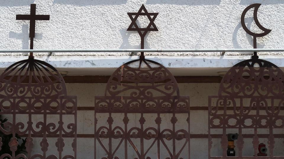 Les symboles des trois religions monothéistes, le christianisme, le judaïsme et l'islam : la croix, l'étoile de David et le croissant de lune.
