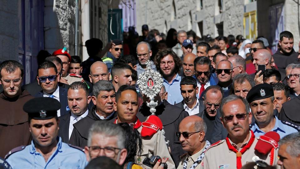Une foule suit la relique en procession dans une rue de Bethléem.
