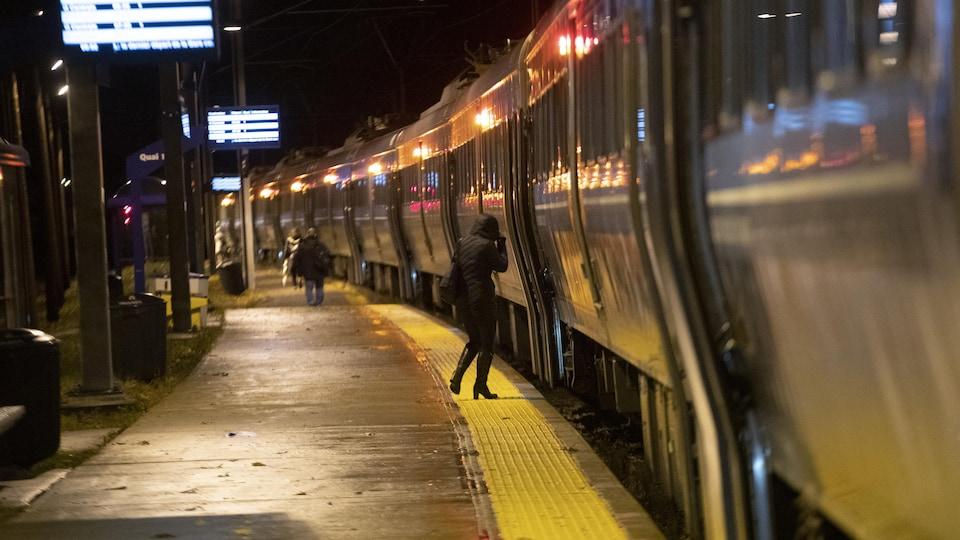 Une femme entre dans un train qui s'apprête à quitter la gare de Deux-Montagnes.
