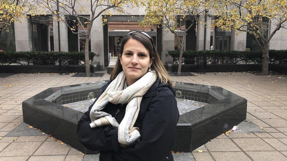 Sylvie Papineau, les bras croisés, dans une cour intérieure.