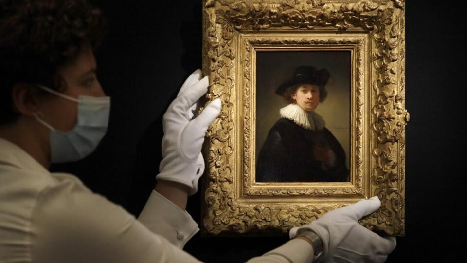 Une personne portant des gants montre l'autoportrait du peintre.