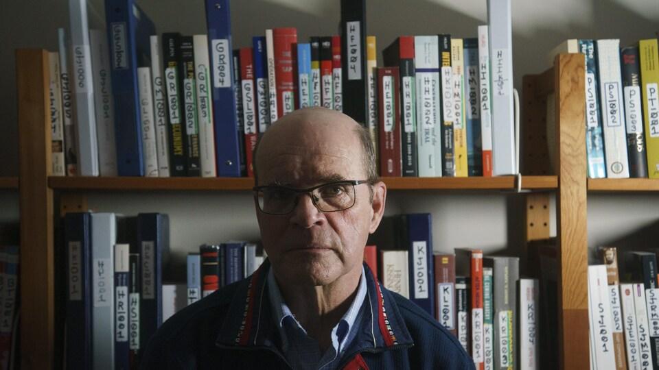 Un homme devant sa bibliothèque.