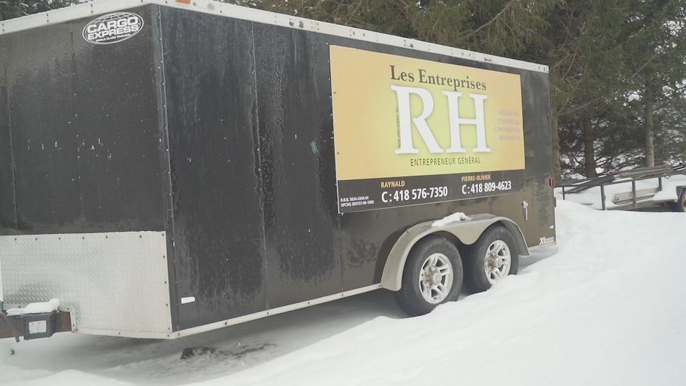La remorque est sous la neige, au pied de sapins