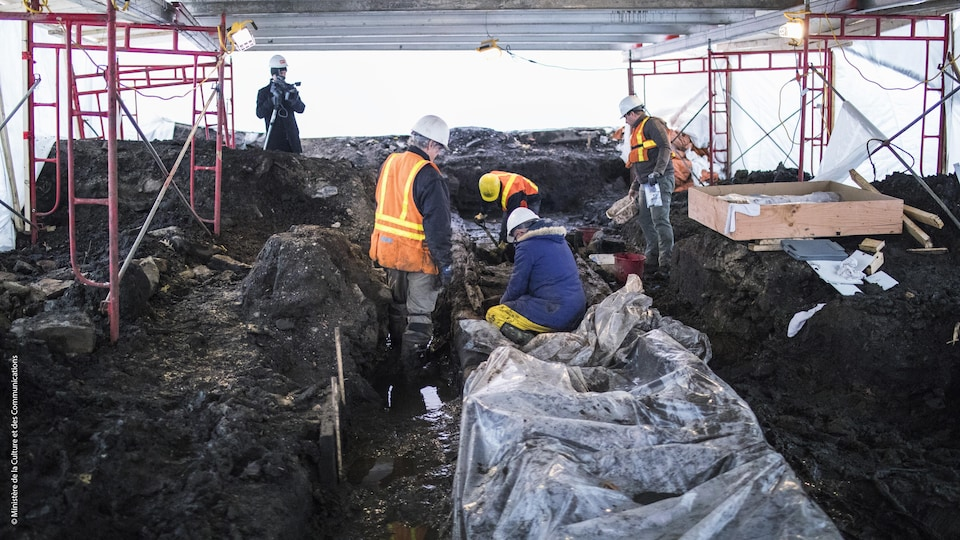 Des conservateurs tentent d'extirper les morceaux du rempart palissadé de Beaucours à Québec de la glaise avant la période de gel