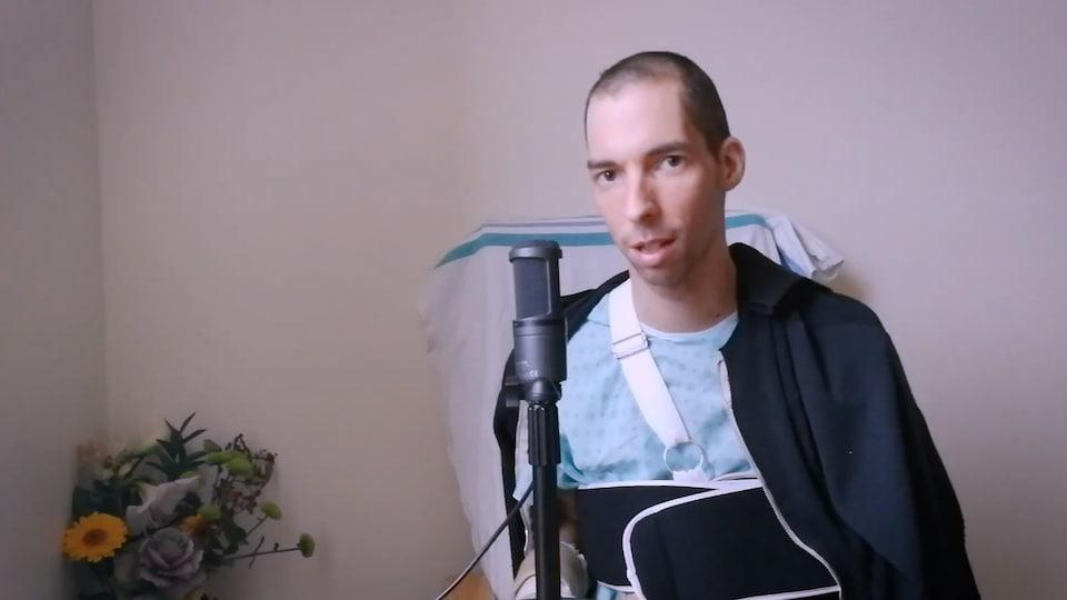 Rémy Bélanger de Beauport devant un micro, dans une chambre d'hôpital