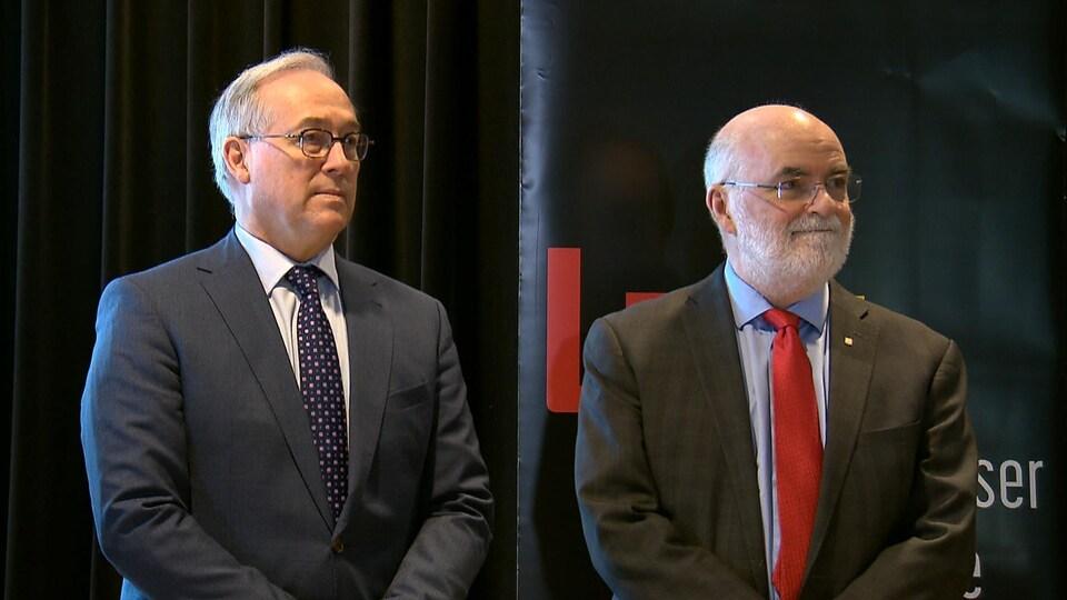 Rémy Normand et Robert Beauregard debout, côte à côte, écoutent l'introduction d'une conférence de presse.