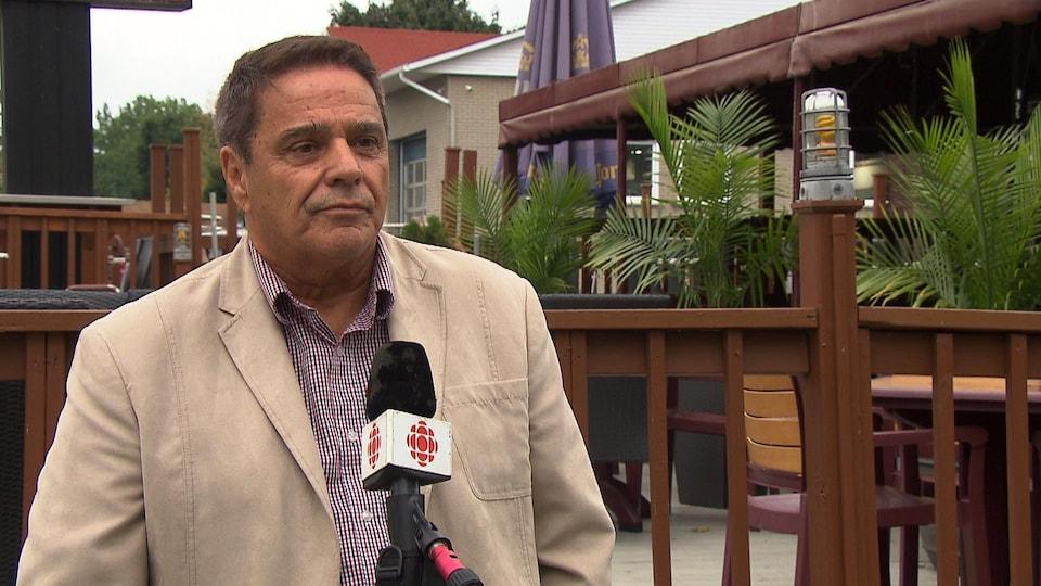 Renaud Poulin porte un veston beige et une chemise à carreaux, il parle devant un micro, il est dehors devant une terrasse d'un restaurant.