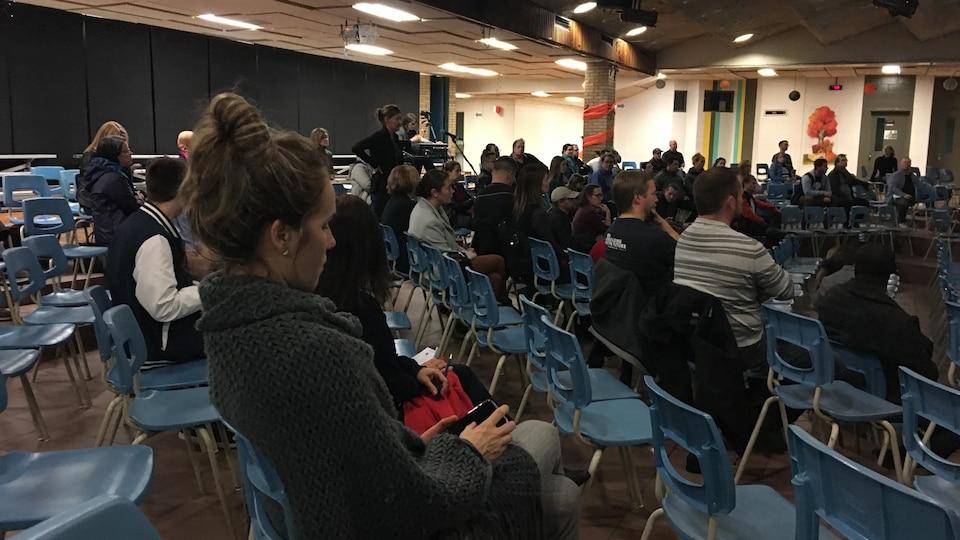 Parents dans une salle qui assistent à une réunion.
