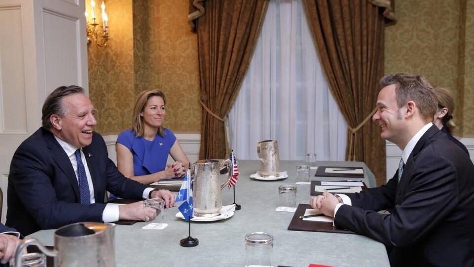 Deux hommes et deux femmes sont assis autour d'une table.