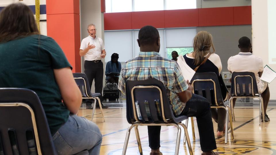 Des gens assis sur des chaises dans un gymnase devant un homme en chemise blanche.