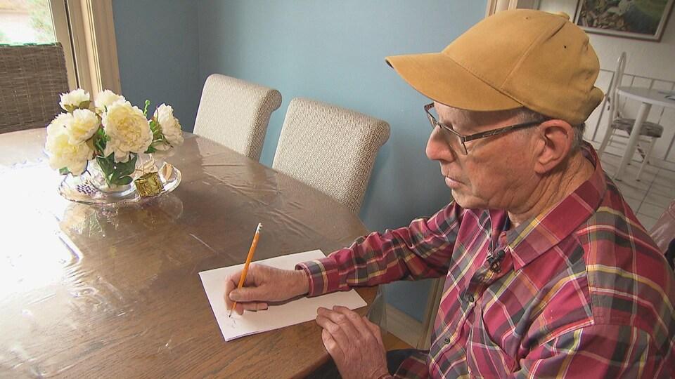 Un homme assis à table tenant un crayon.