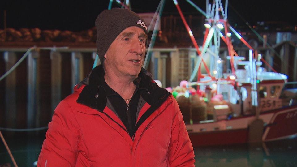 René Landry en entrevue à l'aube au quai de Rimouski devant un bateau de pêche.