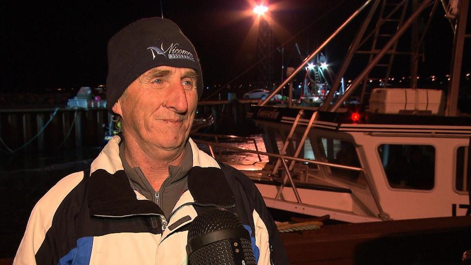 Le pêcheur devant son bateau.